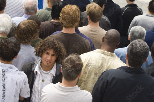Young man standing in crowd