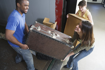 Young man and woman carrying heavy box.