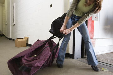 Young woman pulling a huge traveling bag.