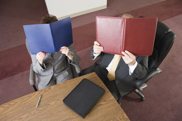 Business people covering their faces with files.
