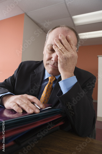 View of an exhausted businessman sitting in an office.