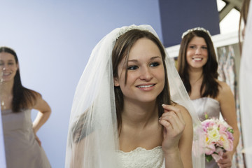 Bride with her bridesmaids looking in a mirror.