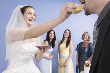 Young bride feeding the groom a piece of cake..