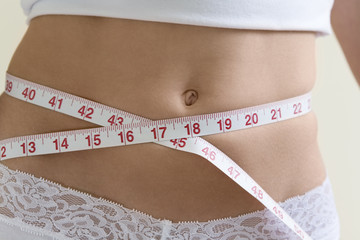 A young woman measuring her waist.