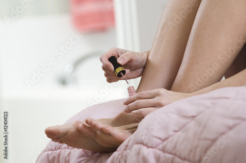 A woman applying nail polish on her nails.