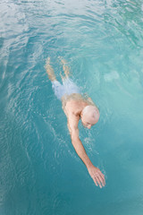 Senior man swimming in a pool