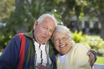 Portrait of a senior couple in a park smiling.