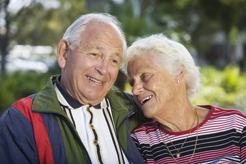 Senior couple smiling in a park.