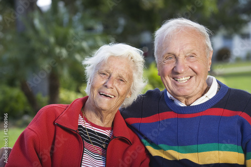 Portrait of a senior couple smiling in a park.