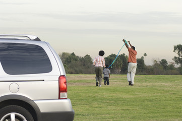 Family with one child 5-6 flying kite