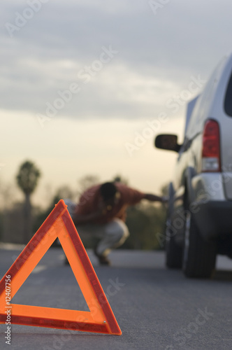 Warning triangle in front of broken down car, man in background
