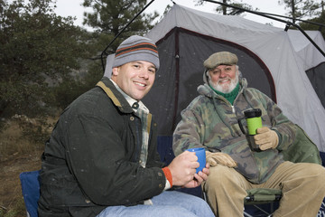Father and son drinking by tent