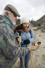 Two people reading a compass on hiking trip