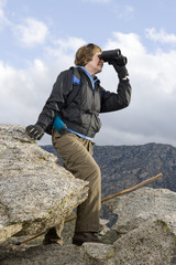 Middle-aged woman standing on rock and using binoculars