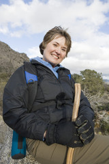 Portrait of middle-aged woman holding hiking pole and smiling