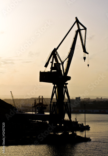 Dockyard crane next to the sea during sunset