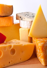 group of Various types of cheese on a wooden board