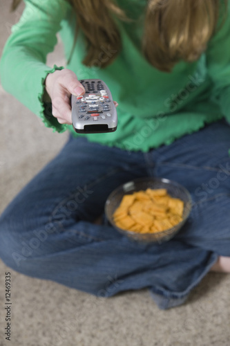 Young girl using a remote and having snacks