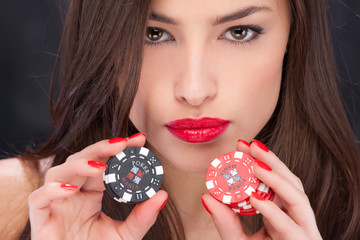 Close up of a pretty woman holding gambling chips