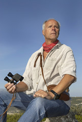 Mature man model posing outdoors with is binoculars