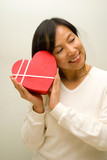 Asian lady closing her eyes with heart shape box gift