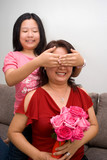Asian girl covering mum's eye with flowers