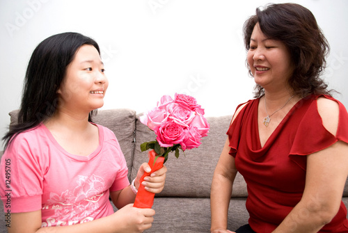 Girl passing bouquet of roses to mother