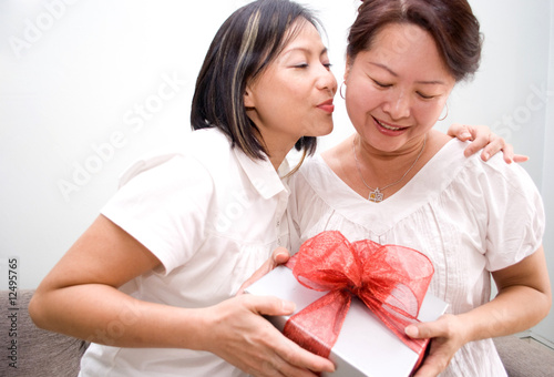 asian lady kissing mother with gift