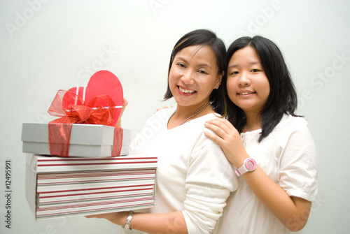 Two female with stack of gifts