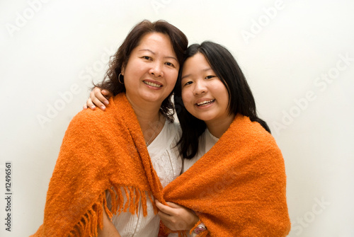 Mother and daughter sharing blanket - love
