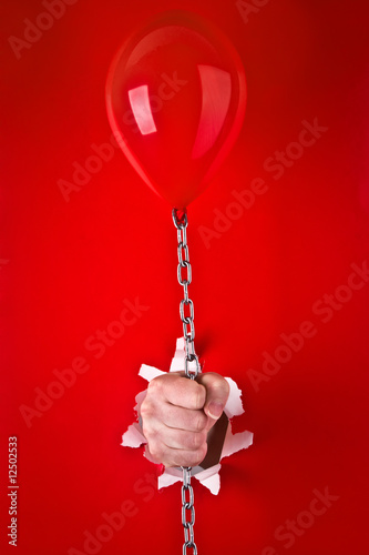 Hand holding red balloon