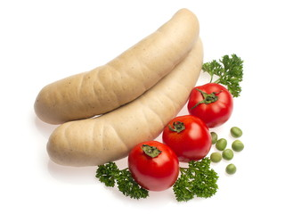 White sausage decorated with tomato, parsley and green pea