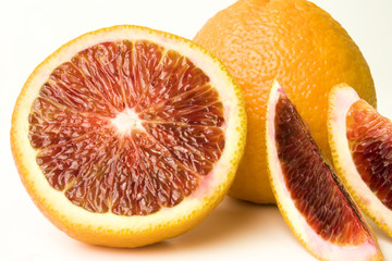 Fresh Whole and sectioned blood oranges close-up