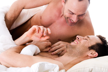 Smiling men couple in bed