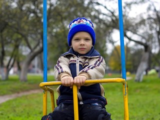 The boy in jackets and cap swing on a seesaw