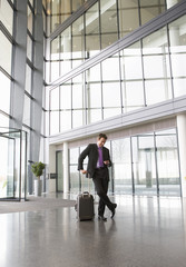 A businessman waiting in an office lobby with a suitcase