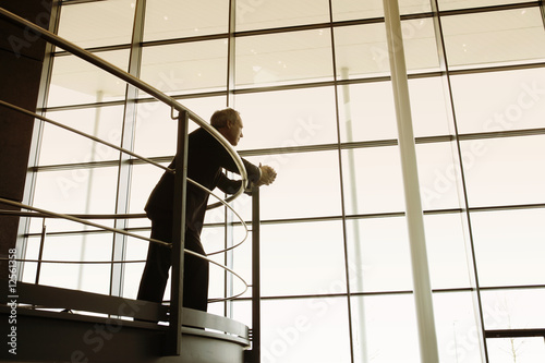 A businessman looking over balcony railings