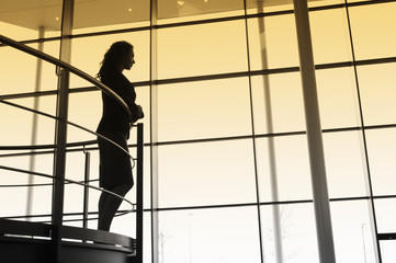 A businesswoman looking over balcony railings