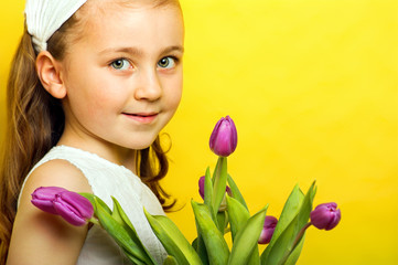 smiling beautiful  young girl with tulips at spring