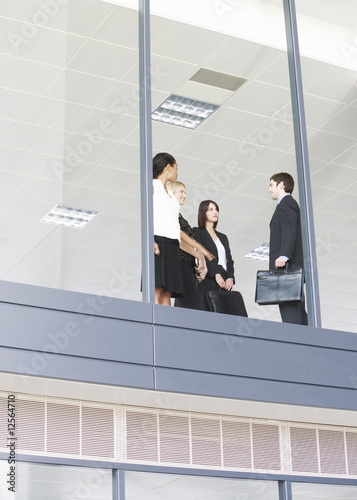 Three business colleagues on upper floor of an office building