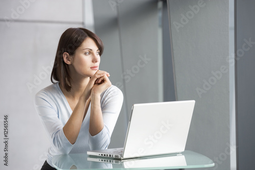 A business woman with laptop, staring out of the window