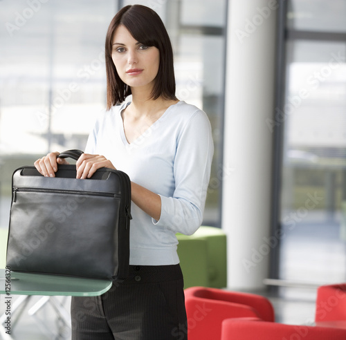 A businesswoman in a modern office, holding a black briefcase