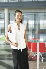A businesswoman standing in a modern office, holding some papers