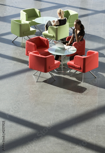 Two businesswomen sitting at tables in an office building