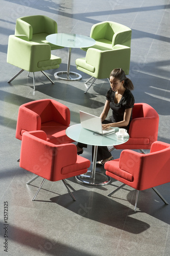 A businesswoman sitting at a table typing on a laptop