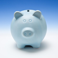 Piggy bank style money box on a blue studio background.