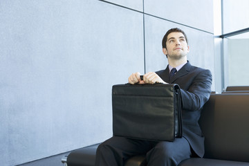 A businessman sitting down waiting holding a briefcase