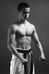 Young sporty karate man doing special exercise. B&W