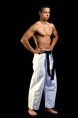 Young sporty karate man doing special exercise on black backgrou