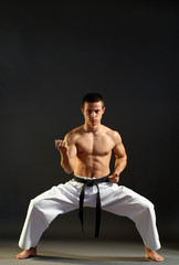 Young sporty karate man doing special exercise on gray backgroun